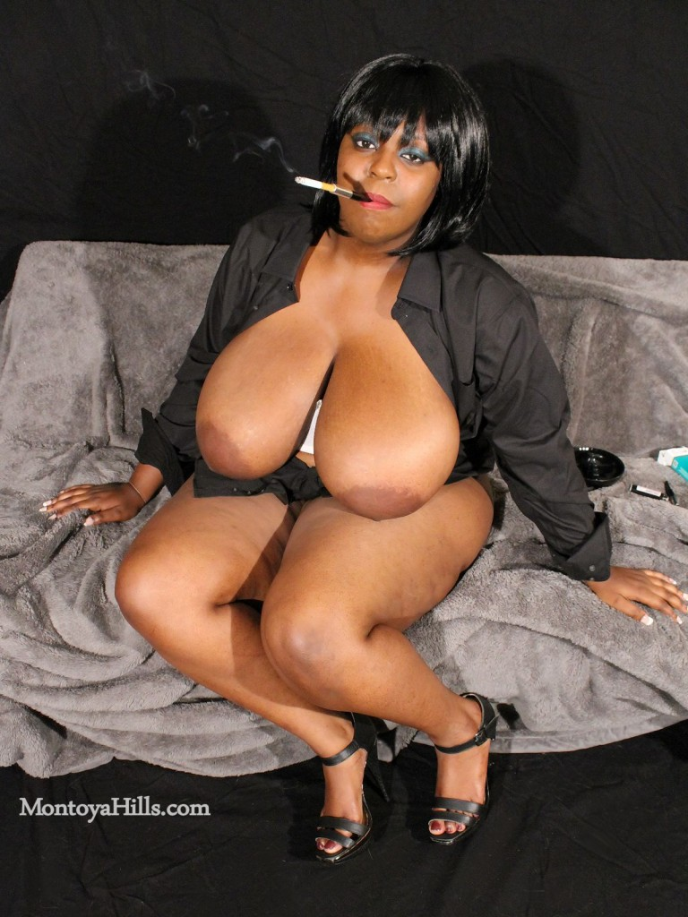 Big tit ebony milf smoking a cigarette with her big tits and large areolas exposed.