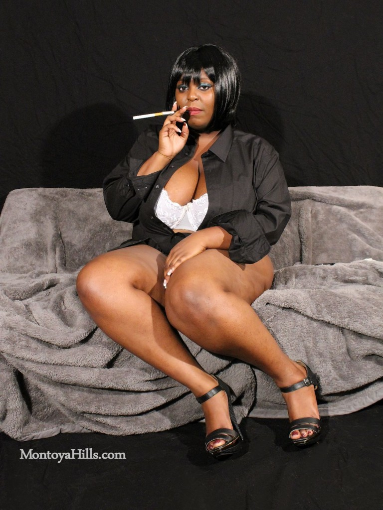 Big tit ebony milf, Montoya Hills, is smoking a cigarette in high heels showing her deep cleavage.