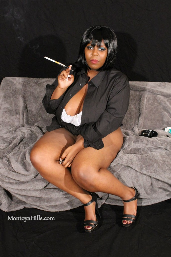 Big tit ebony milf smoking a cigarette and showing cleavage.