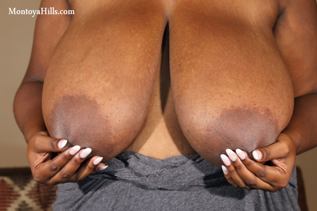 Laege black aerolas and nipples, pinched by long finger nails.