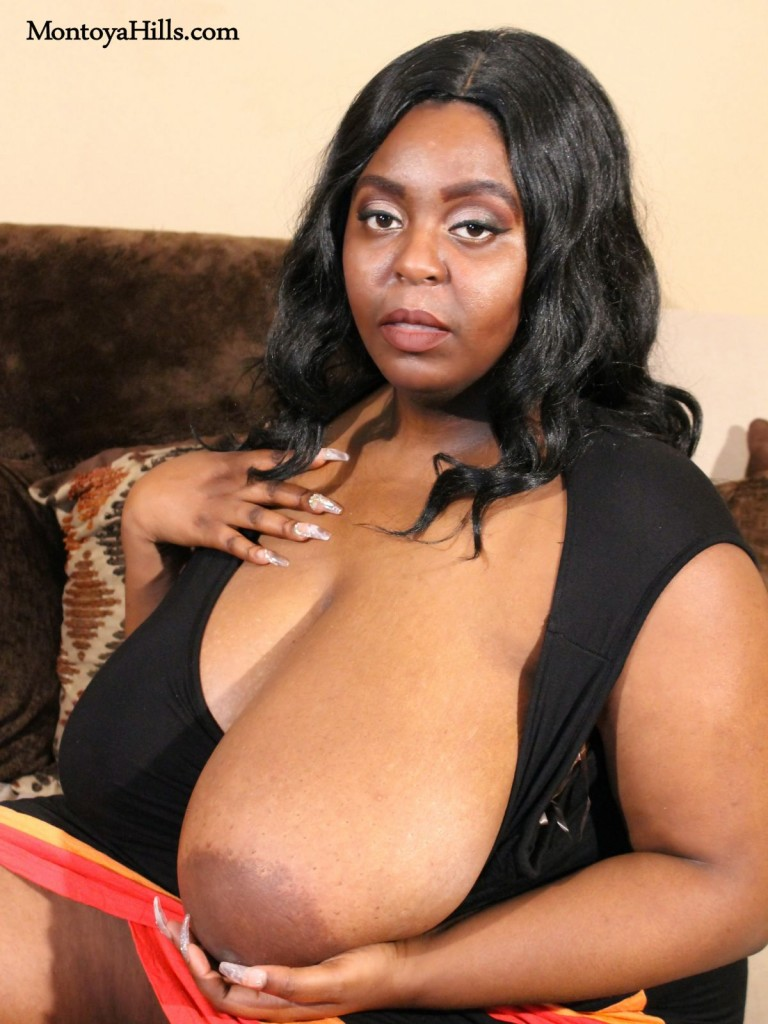 Ebony milf with large areolas and long finger nails  cupping her boob.